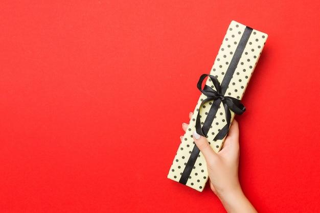 Die hände der frau, die gestreifte geschenkbox mit farbigem band auf rotem hintergrund halten. weihnachtskonzept oder anderer handgemachter präsentkarton des feiertags, draufsicht des konzeptes mit kopienraum