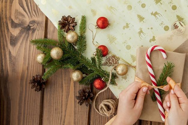 Die hände der frau, die oben weihnachtsgeschenk, abschluss einwickeln. unvorbereitete weihnachtsgeschenke auf hölzernem mit dekorelementen und einzelteilen, draufsicht. weihnachten oder neujahr diy verpackung.