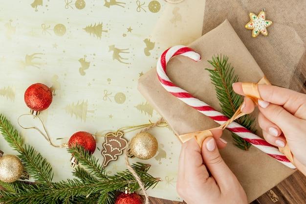 Die hände der frau, die oben weihnachtsgeschenk, abschluss einwickeln. unvorbereitete weihnachtsgeschenke auf holz