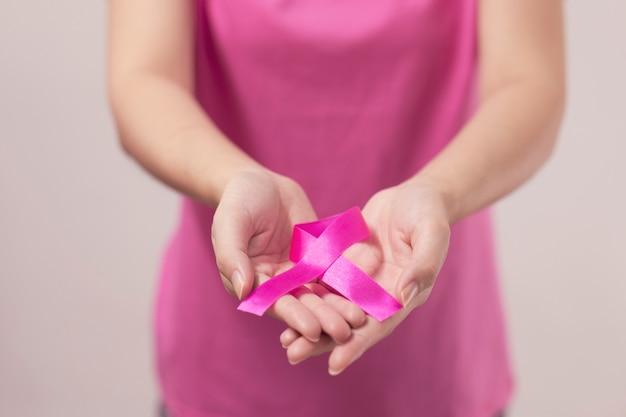 Die hände der frau, die rosa brustkrebsband halten.