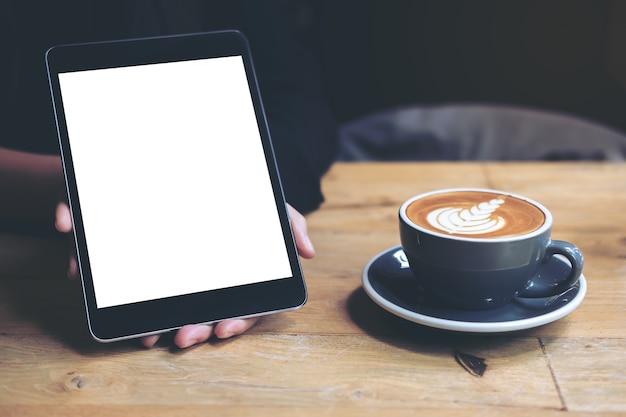 Die hände der frau, die schwarze tablette mit weißem leerem bildschirm und kaffeetasse auf holztisch zeigen