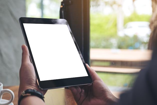 Die hände der frau, die schwarzen tabletten-pc mit weißem leerem bildschirm und kaffeetasse halten