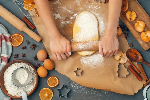 Die hände der frau, die teig für kekse vorbereiten, schließen