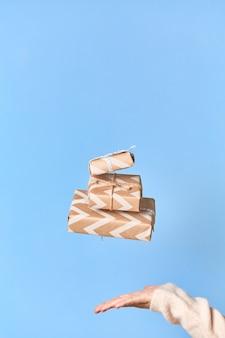 Die hände der frau, die versuchen, geschenkbox zu fangen. weihnachten oder neujahr dekoriert geschenkbox.