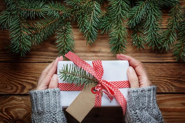 Die hände der frau, die weihnachtsgeschenk im papierweiß mit rotem band halten