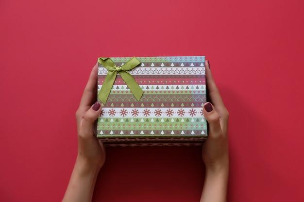 Die hände der frau, die weihnachtsgeschenk verziert auf draufsicht des roten hintergrundes halten