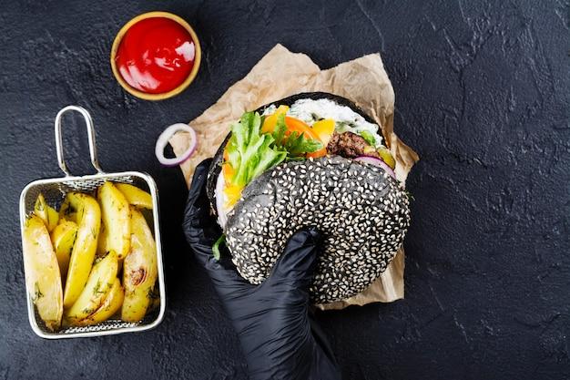 Die hände der frau in den schwarzen gummihandschuhen halten saftigen schwarzen brötchenburger