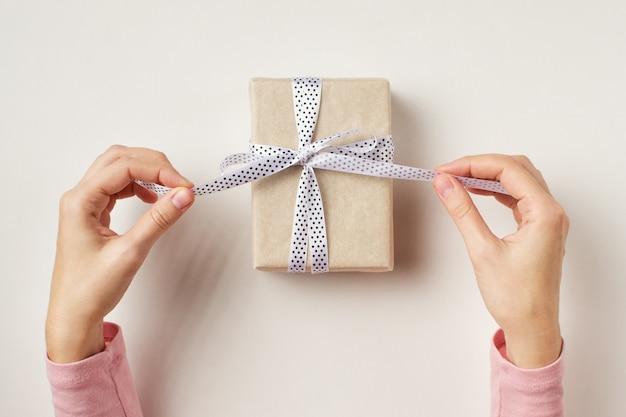 Die hände der frau lösen bogen auf geschenkbox auf weißem hintergrund, draufsicht