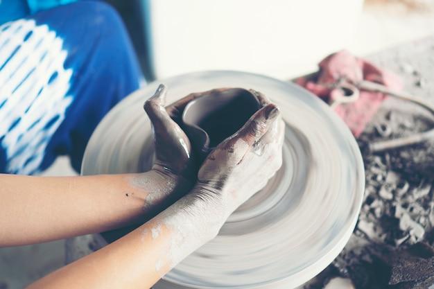 Die hände der frau schließen sich, das meisterhafte atelier der keramik arbeitet mit ton auf einer töpferscheibe