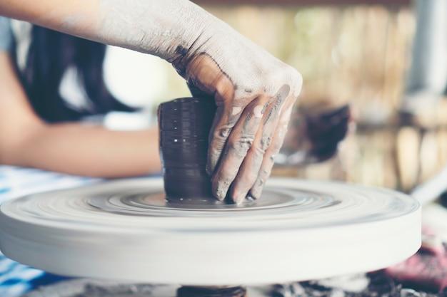 Die hände der frau schließen sich, das meisterhafte atelier der keramik arbeitet mit ton
