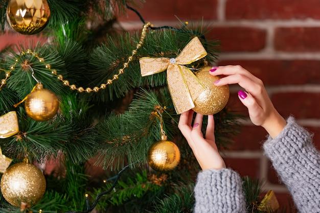 Die hände der frau schmücken weihnachtsbaum durch goldenes spielzeug