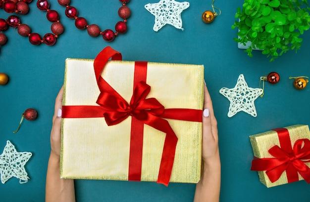Die hände der frau und weihnachtsgeschenkbox.