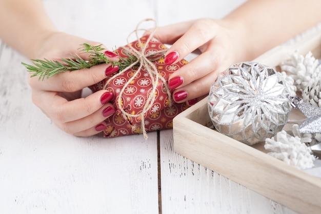 Die hände der frau wickeln handgemachtes geschenk des weihnachtsfeiertags im kraftpapier mit schnurband ein