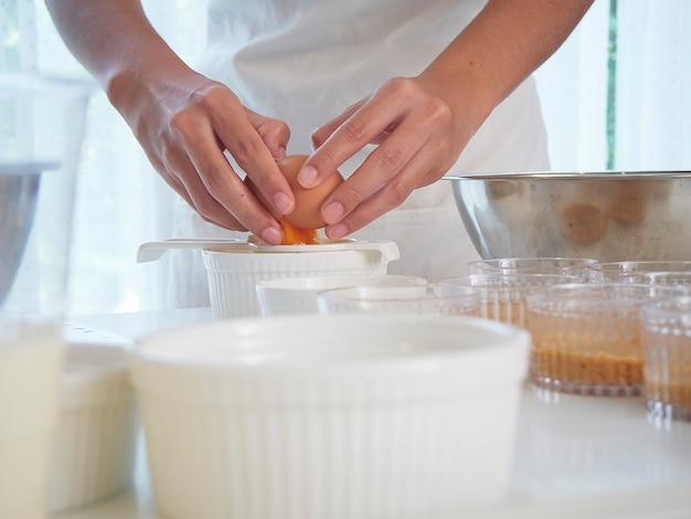 Die hände der frauen bereiten kuchenbestandteile vor