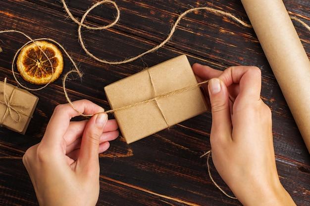 Die hände der frauen, die ein geschenk vom kraftpapier machen.