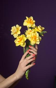 Die hände der frauen, die einen blumenstrauß halten. frühlingsblumen narzissen. weiblicher feiertag