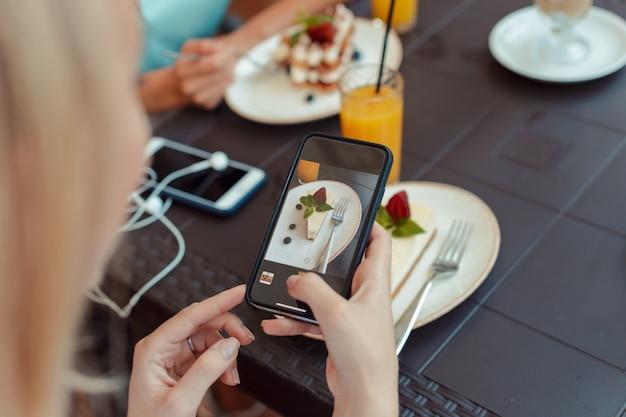 Die hände der frauen, die foto von der süßspeise am handy beim sitzen im bequemen restaurant machen