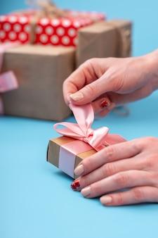 Die hände der frauen, die geschenkbox halten, verpackten im kraftpapier mit rosa band