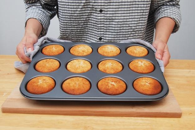 Die hände der frauen, die metallform mit muffins halten.