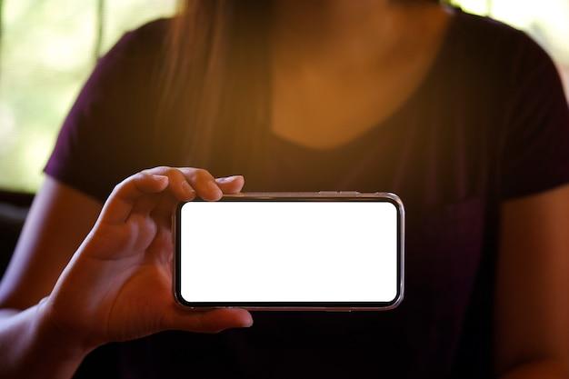 Die hände der frauen, die vorwärts leeren bildschirm des mobiltelefons für kopienraumschirm halten