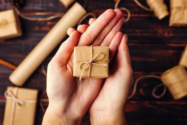 Die hände der frauen halten ein geschenk des kraftpapiers vor dem hintergrund der getrockneten orange, des zimts, der kiefernkegel, des anises auf einem holztisch.
