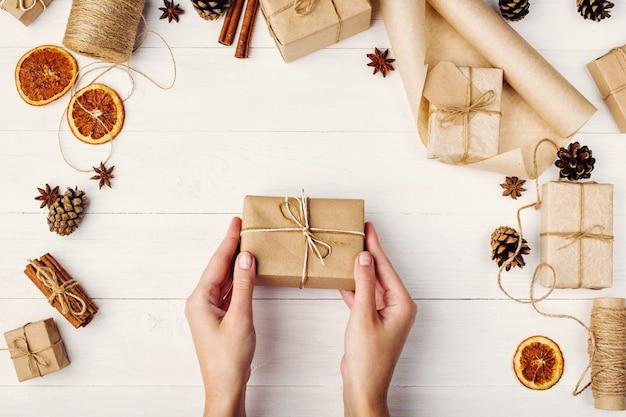 Die hände der frauen halten ein geschenk des kraftpapiers vor dem hintergrund der getrockneten orange, des zimts, der kiefernkegel, des anises auf einer weißen tabelle.