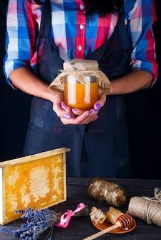 Die hände der frauen halten ein glasgefäß mit blumen-, organischem honig auf einem dunklen hintergrund