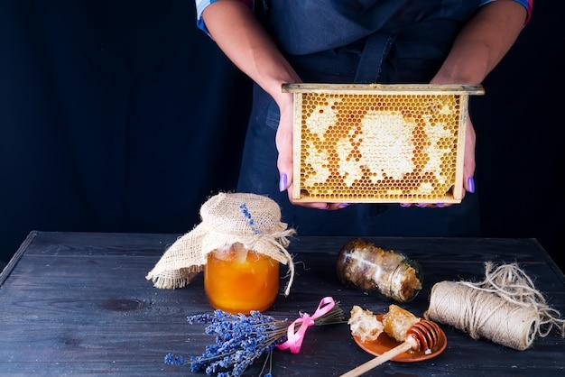 Die hände der frauen halten honigkämme mit organischem honig auf einem dunklen hintergrund.