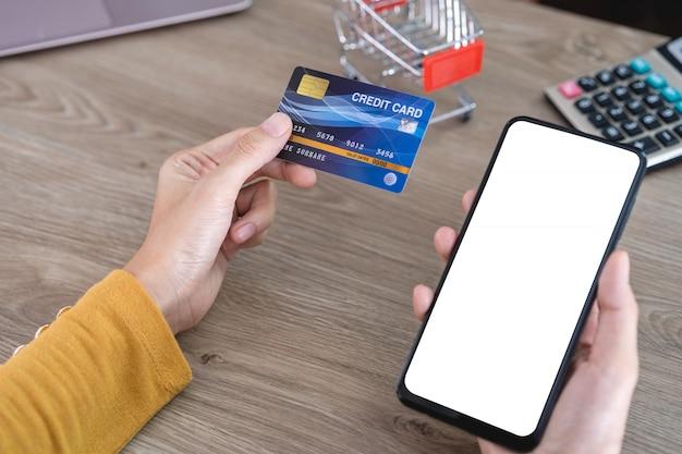 Die hände der frauen im gelben hemd, das handy mit leerem bildschirm und kreditkarte auf schreibtisch hält und handy für das on-line-einkaufen, internetbanking, on-line-handel verwendet