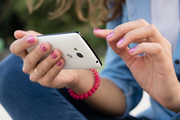 Die hände der frauen mit der roten maniküre, die einen modernen handy mit einem touch screen hält