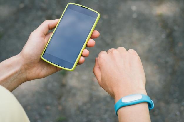 Die hände der frauen mit einem sportarmband und einer smartphone-nahaufnahme im freien
