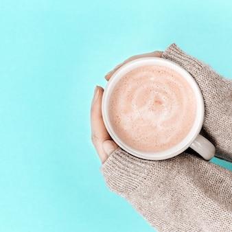 Die hände der frauen mit tasse kaffee über tendenz färben oberfläche des blauen papiers. süßer heißer wohlriechender cappuccinoabschluß oben. sicht von oben.