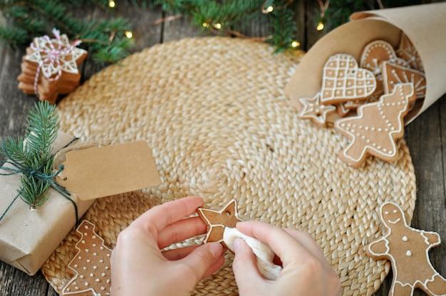 Die hände der frauen verzieren weihnachtslebkuchenplätzchen mit dem zucker, der auf schönem hölzernem bereift.
