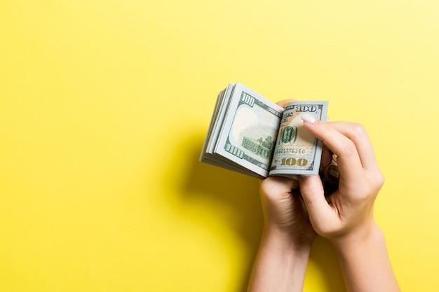 Die hände der geschäftsfrau, die hundert dollarscheine auf buntem zählen. gehalt und lohn copyspace. draufsicht investition