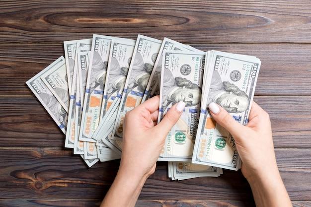 Die hände der geschäftsfrau, die hundert dollarscheine auf buntem zählen. gehalt und lohn. draufsicht investition