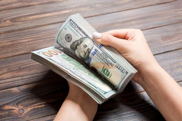 Die hände der geschäftsfrau, die hundert dollarscheine auf hölzernem zählen. gehalt und lohn. perspektivische ansicht investition