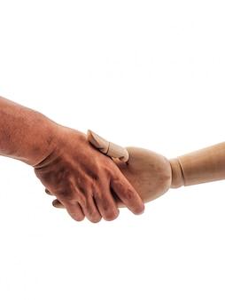 Die hände der hölzernen puppe halten an zur menschlichen hand auf weiß