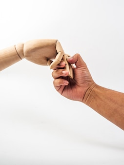 Die hände der hölzernen puppe halten an zur menschlichen hand auf weißem hintergrund