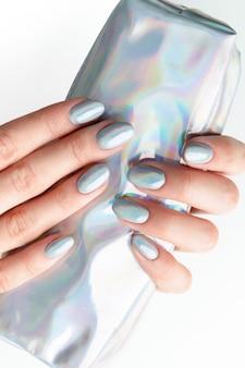 Die hände der jungen erwachsenen frau mit holographischen modischen nägeln