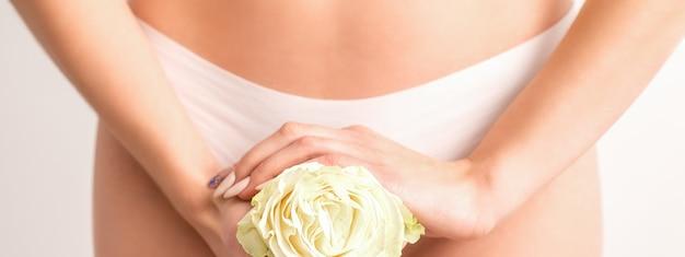 Die hände der jungen frau, die eine weiße blume halten, die epilatbikinizone bedeckt, lokalisiert auf weißem studiohintergrundkonzept der reproduktiven gynäkologie der weiblichen gesundheit