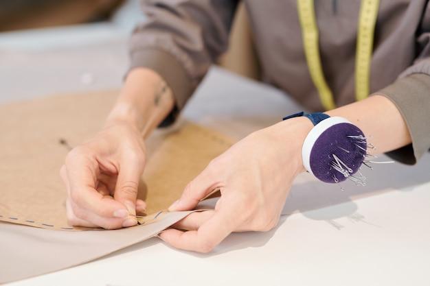 Die hände der jungen näherin, die feststecken, schneiden skizze zu textil, während sie über neuem kleidungsmodell in der werkstatt arbeiten