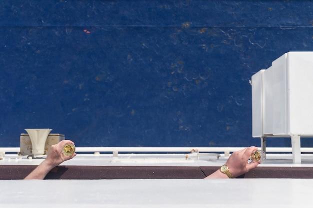 Die hände der männer, die gläser wein auf einem hintergrund des blauen schiffsdecks halten
