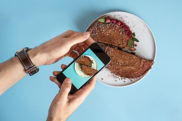 Die hände der männer machen ein foto von einem schokoladenkuchen auf ihrem smartphone auf einem blauen hintergrund. bloggen und essen fotos.