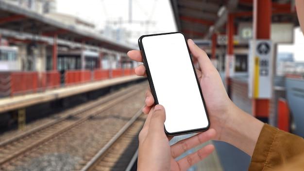 Die hände der nahaufnahmemontagefrau, die smartphone auf bahnübersetzung in japan halten.