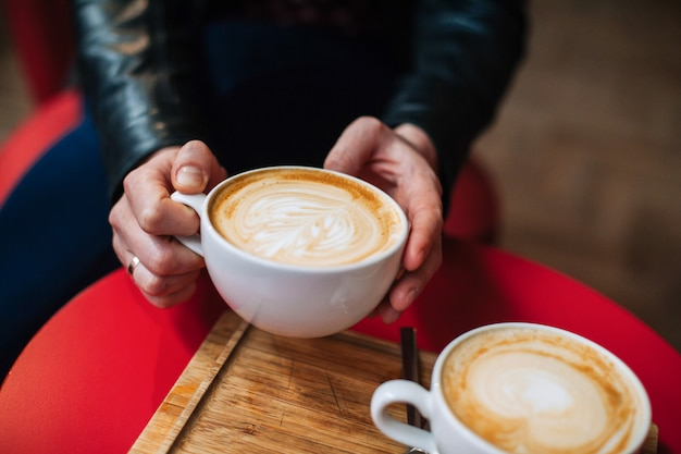 Die hände der person, die eine schale heißen cappuccino am café beim trinken des kaffees halten.