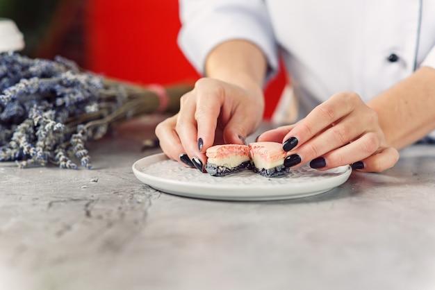 Die hände der weiblichen konditorin in der nähe halten einen halbgeschnittenen rosa und grauen macaron auf einem weißen teller.