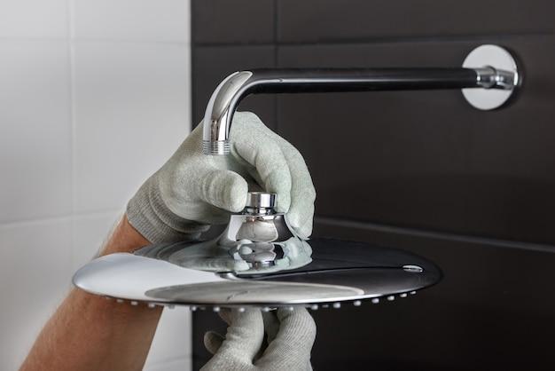Die hände des arbeiters installieren den kopf des eingebauten duschhahns.