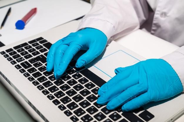 Die hände des arztes in medizinischen handschuhen liegen auf der tastatur der arzt tippt text auf dem computer ein ...
