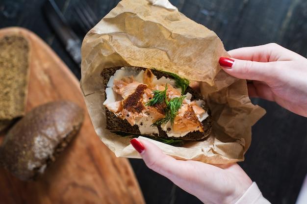 Die hände des chefs, der das skandinavische sandwich mit geräuchertem lachs auf schwarzbrot mit weichkäse hält