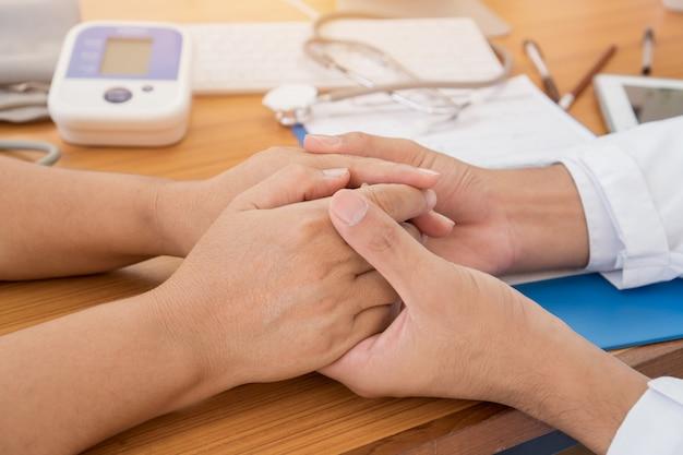 Die hände des doktors, die weibliche geduldige hand für die beruhigung mit freundlicher ermutigungsempathie für hoffnungsunterstützung nach ärztlicher untersuchung am hostpital und den schlechten nachrichten des doktors für zujubelnde vertrauensbehandlung halten